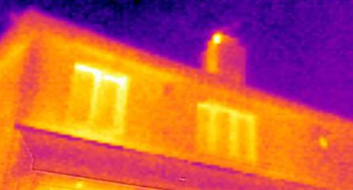 Thermal imaging cameras capture an image of a chimney stack that's been warmed by air rising out of the house.